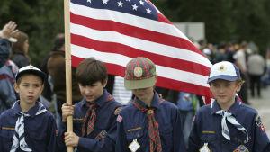 Fyra pojkar i scoutkläder står på rad. En av dem håller i den amerikanska flaggan. Resten tittar åt sidan eller neråt.