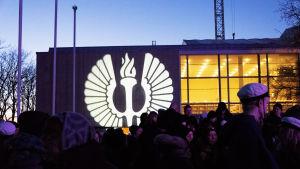Folksamning framför Åbo Universitet, på en vägg lyser Åbo Universitets logo.