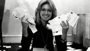 Olivia-Newton John laskee äänikirjekuoria Euroviisuissa 1970-luvulla mustavalkoisessa kuvassa.