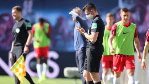 Fjärdedomaren Alexander Sather använder sig av ett andningsskydd under matchen mellan Leipzig och Freiburg.