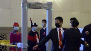 Folk går igenom en säkerhetskontroll för att komma in på folkkongressen i Kina. I förgrunden en man som iklädd andningsskydd och kostym går igenom en metalldetektor.