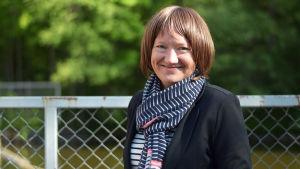 En bild på en kvinna i randig halsduk och mörk jacka. Hon ler mot kameran och i bakgrunden syns ett metallstaket och grönska.