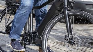 En person med blå skor är på väg att starta med sin svarta elcykel.