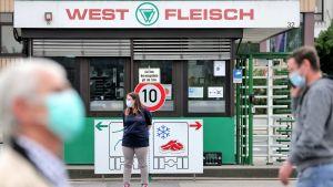 Människor i ansiktsmasker utanför livsmedelsföretaget Westfleisch i Hamm i Tyskland.