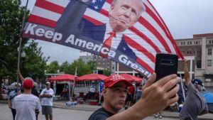 Trumpsupportrar viftar med en jätteflagga med presidentens bild.