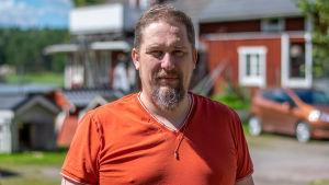 en porträttbild på en medelåldersman i orange skjorta.
