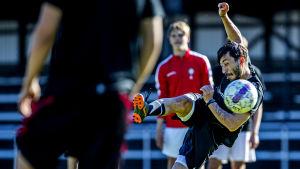 En fotbollsspelare sparkar en boll.