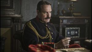 Georges Picquart sitter vid sitt skrivbord, iklädd uniform, och ser bekymrad ut.
