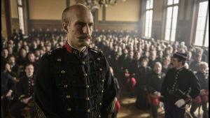 En gråhårig Alfred Dreyfus står i en domstolssal iklädd militäruniform, med en stor publik bakom sig.