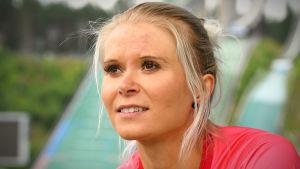 Mari Eder sitter på läktaren på stadion i Lahtis och blickar ut över stadion