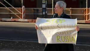 En kvinna håller upp ett plakat där det krävs att bygget av den rysk-tyska gasledningen Nord Stream 2 stoppas