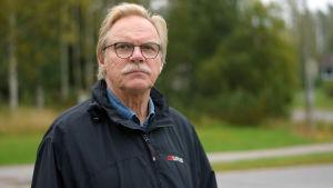En äldre man med mustasch och glasögon. Står ute. Klädd i mörkblå jacka.