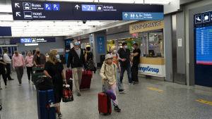 Personer med resväskor går på Helsingfors-Vanda flygplats.