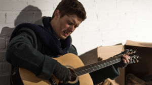 Ledsen man spelar gitarr för sig själv.