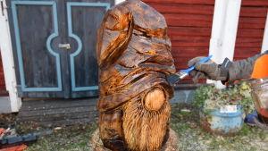 En träskulptur som föreställer en tomte oljas in med pensel.