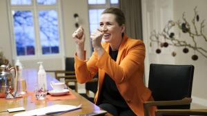Statsminister Mette Frederiksen håller upp händerna i hurrarop när hon via videolänk följer med den första vaccinationen i Danmark.