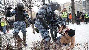 En person blir fälld till marken av polis i samband med demonstration i Ryssland.