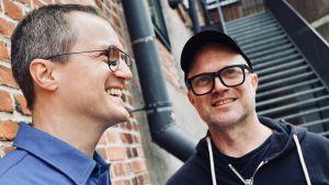 Icons of Elegance, bröderna Anssi och Henri Växby, står vid en tegelmur och skrattar.