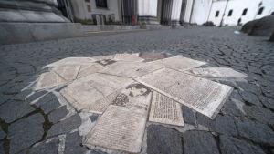 Ett minnesmärke bestående av flygblad på en gata.