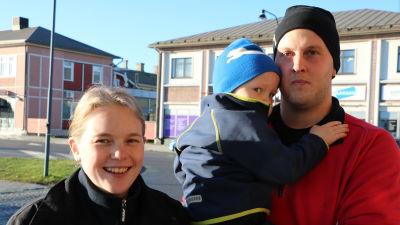 803f20dcec2d En ung leende kvinna står bredvid en ung man som håller ett barn i famnen.