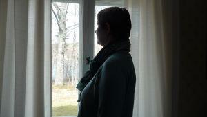 Lotta Andström  till hälften med ryggen svängd mot kameran. Hon tittar ut genom ett fönster. Ute är det vårsol. Långa vita gardiner i fönstret.