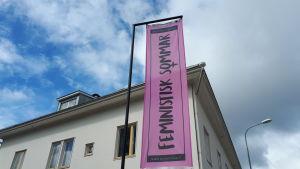 Rosa banderoll med texten Feministisk sommar.