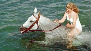 Kristina Söderbaum ratsastaa vedessä. Kuva natsi-Saksan ajan elokuvasta Muuttolintu (Opfergang, 1944).