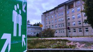 En stor gammal stenbyggnad i flera våningar, grå. TIll vänster en grön skylt med två vita mänskofigurer i mitten och pilar runt omkring som visar att man vid nödfall ska samlas på den här platsen.