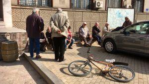 Pensionärer träffas på torget i Veles i Makedonien. En har lämnat sin cykel liggande på trottoaren.