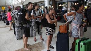 Turister köar på flygplatsen i Lombok.