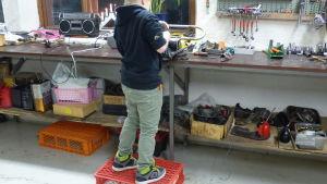 en ung pojke står på en plastpall för att kunna nå upp till verkstadsbordet. Står med ryggen till och blästrar en mopeddel