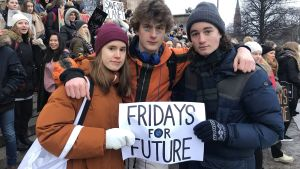 Tre demonstranter står med ett plakat i handen: Fridays for future.