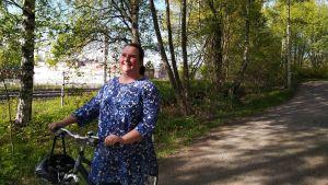 En leende kvinna står med sin cykel på en sandväg. I bakgrunden finns gröna träd och järnvägsspåret skymtar.