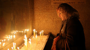 En armenisk kvinna tänder ljus i n kyrka för att hedra minnet av armenierna som dödades i det Osmanska riket mellan år 1915 och år 1917