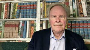 Kaj Bärlund fotograferad framför tapet som liknar en bokhylla på kafé i Borgå.