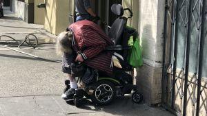 Hemlös kvinna sitter i sin rollator i stadsdelen Tenderloin i San Francisco.