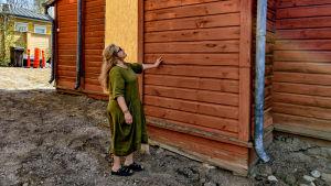 En kvinna står och haller handen på en röd husvägg.