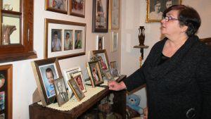 Nainen katselee vanhoja valokuvia seinällä.