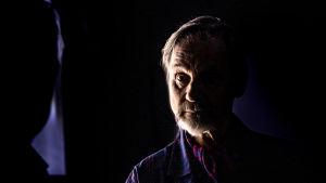 """Asko Sarkola fotograferad i ett mörkt rum i pjäsen """"Pappan"""". Sarkola ser sig själv i spegeln och endast halva av hans ansikte syns medan den andra är täckt av mörkret."""
