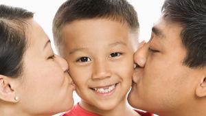 en mamma och en pappa kysser deras son