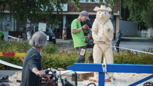 Nainen pyörällä katsoo miestä joka veistää kulmahiomakoneella karhun mallista puuveistosta.