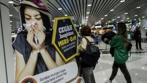Ihmisiä lentokentällä. Kyltti, jossa varoitetaan viruksesta.