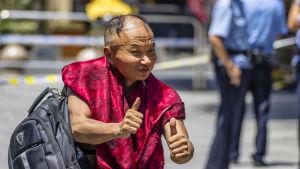 Tunhårig kinesisk man i röd skjorta gör tummen upp mot kameran. I bakgrunden står polis.