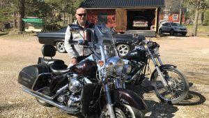 Johan Lindberg poserar vid sin motorcykel
