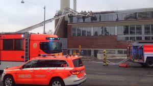 Uttryckningsfordon står parkerade utanför Mejlans sjukhus i Helsingfors. Brandmän jobbar med att släcka branden.