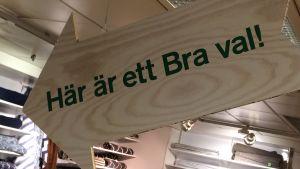 """En stor pilformad skylt hänger i taket av en affär och pekar mot en hylla med texten """"Här är ett Bra val""""."""