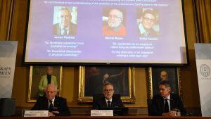 Tre män sitter framför ett skrivbord och berättar vem som vunnit Nobelpriset i fysik. Bakom dem syns bilderna på de tre vinnarna.