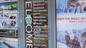 Dörr med välkommen på flera språk för turister