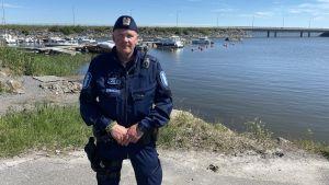Poliskonstapel poserar i en hamn.