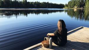 Ung kvinna sitter på en brygga vid Gallträsk i Grankulla med en korg och en termos bredvid sig.